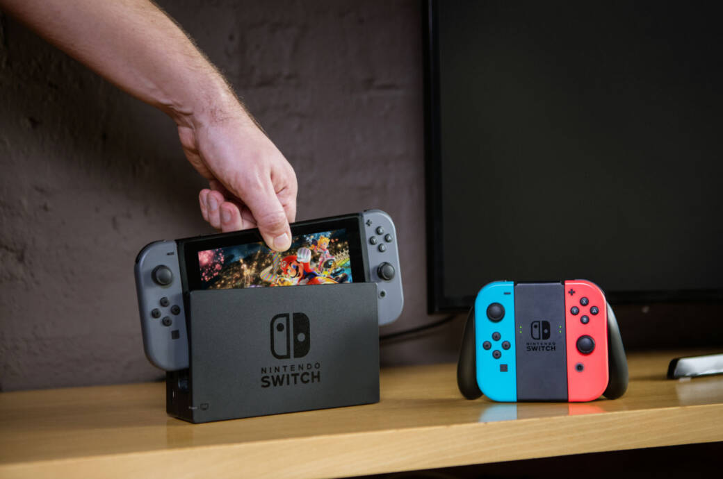 Nintendo Switch in Black being docked next to Blue and Red Joycon Controller